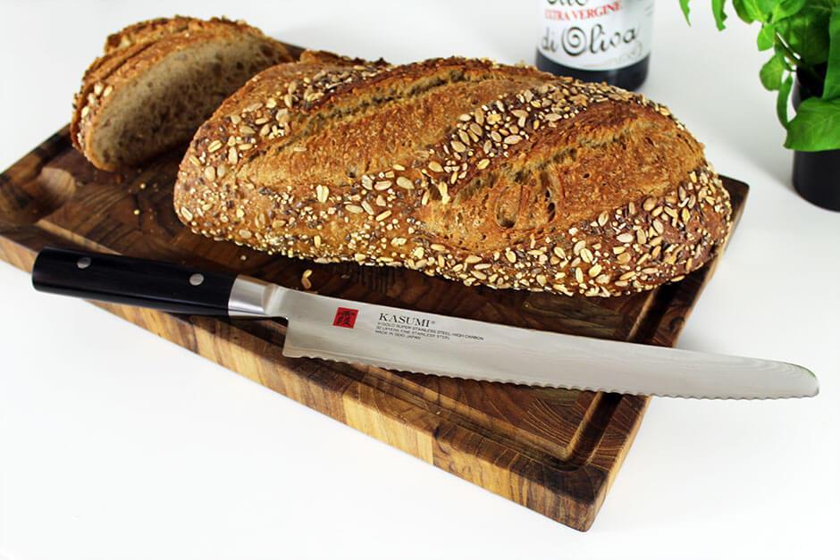 Japansk Brødkniv fra Kasumi på skærebræt med forskellige brød
