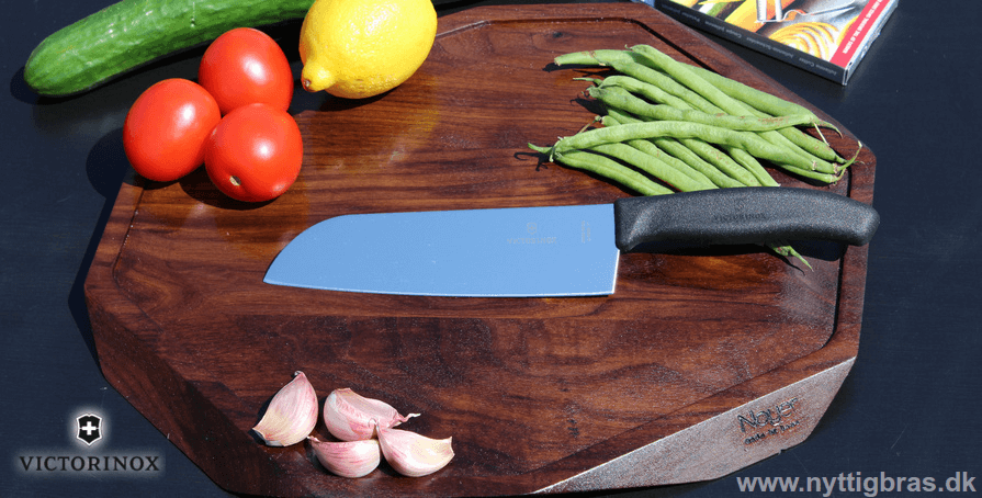 Victorinox Santoku Kokkekniv på Noyer Skærebræt med lækre grøntsager