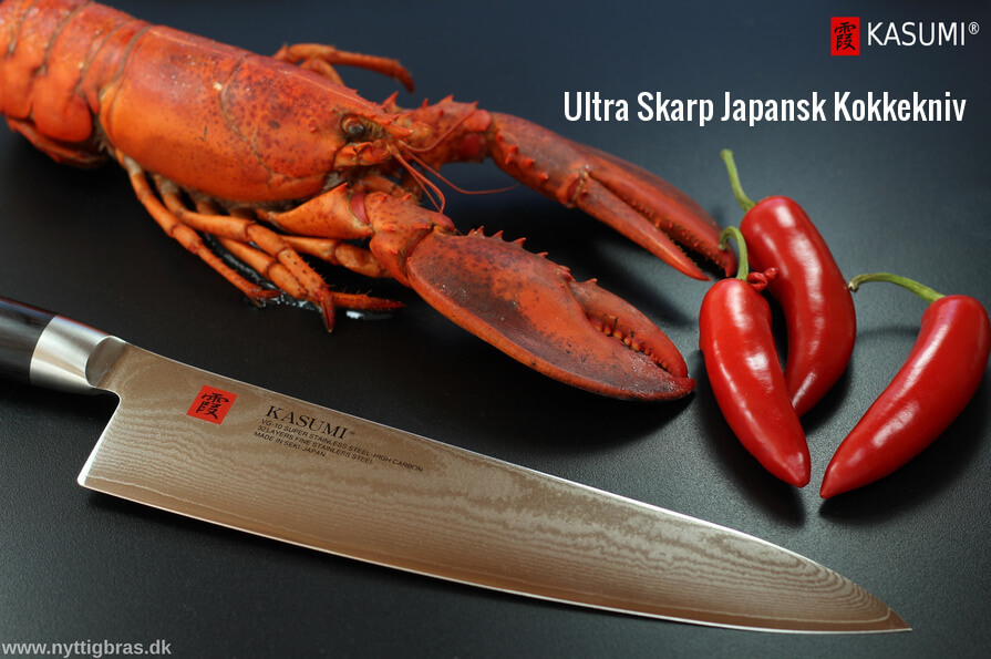 Præsentation af skarp japansk kokkekniv ved siden af hummer og rød chili