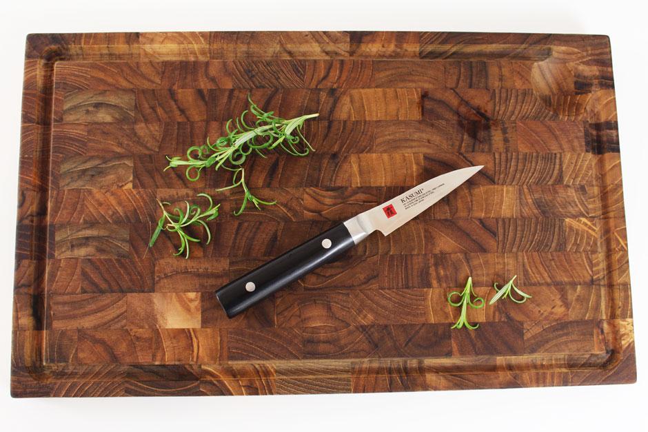 Kasumi Urtekniv på et skærebræt med friske grøntsager og krydderier